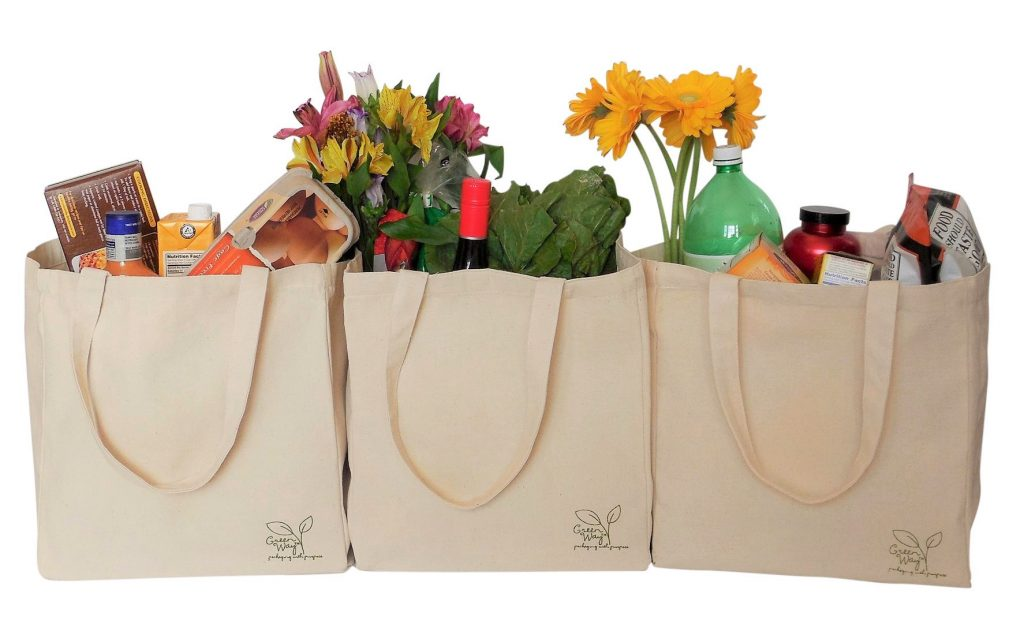 three cotton shopping bags full of groceries
